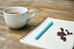 כוס קפה בצד ופולי קפה ועט על מחברת